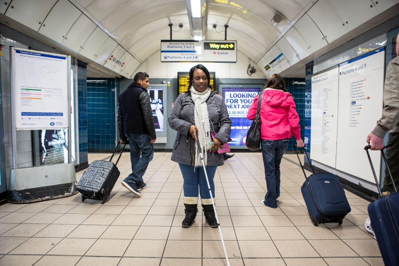 Woman with vision impairment navigating London Underground
