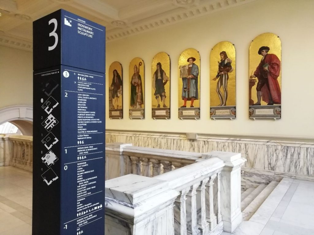View of wayfinding totem against a view of artefacts in the V&A Museum