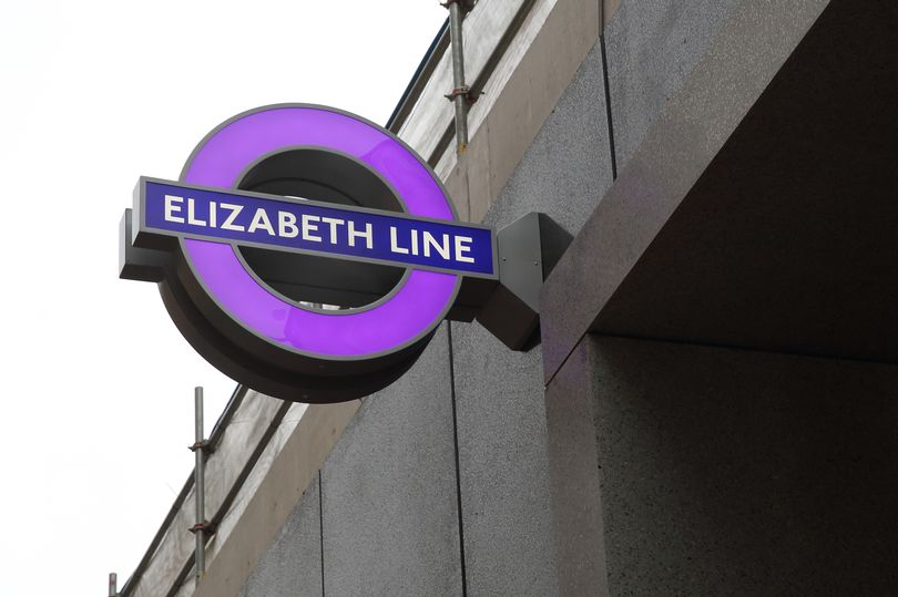 External shot of iconic London Underground signage (featuring purple Elizabeth Line)