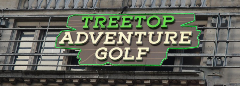 Daytime view of the Treetop Adventure Golf signage displayed on the exterior facade of Manchester Printworks