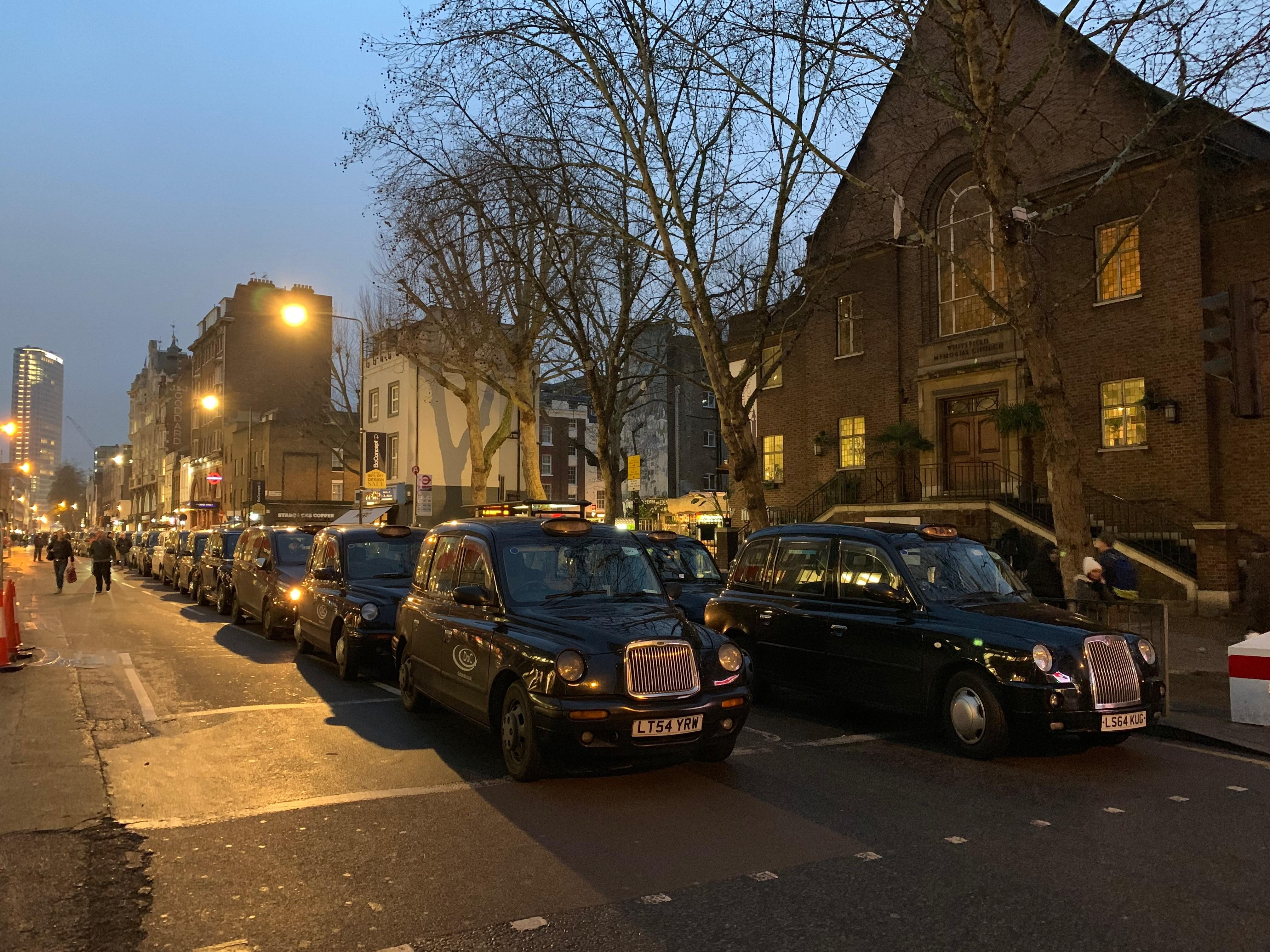 View of a group of London Black Cabs stationary on a street at dusk