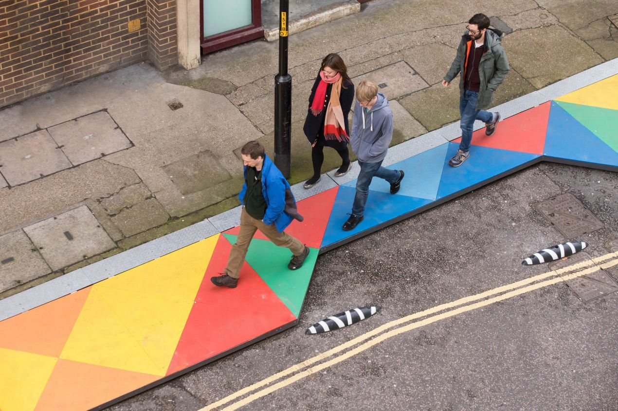Aerial view of people walking along a multi-coloured geometric designed 'boardwalk' in an urban setting