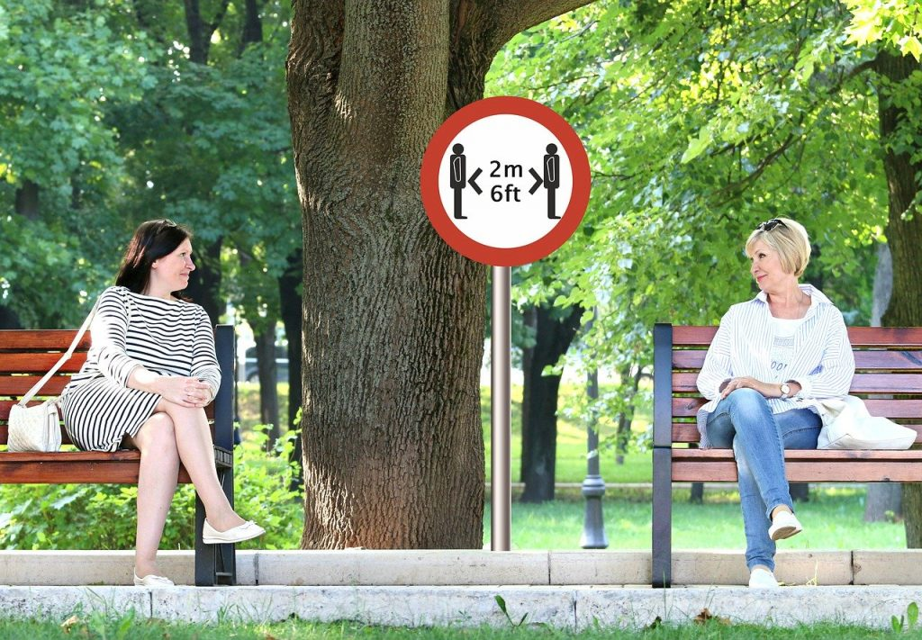 An image of two women sitting on benches in a park with a two metre apart social distancing sign between them