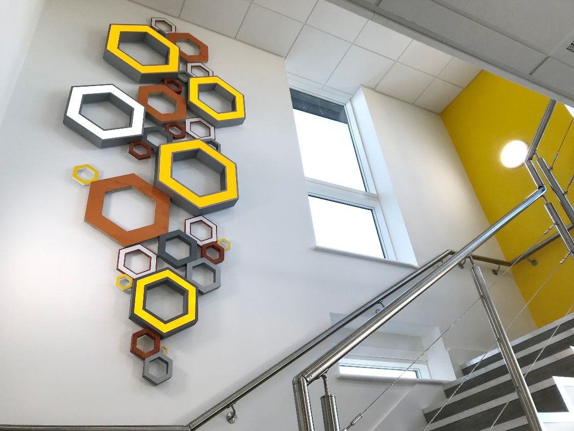 Hexagonal sign branding adorning an internal wall up a staircase in the Telford Mann office building