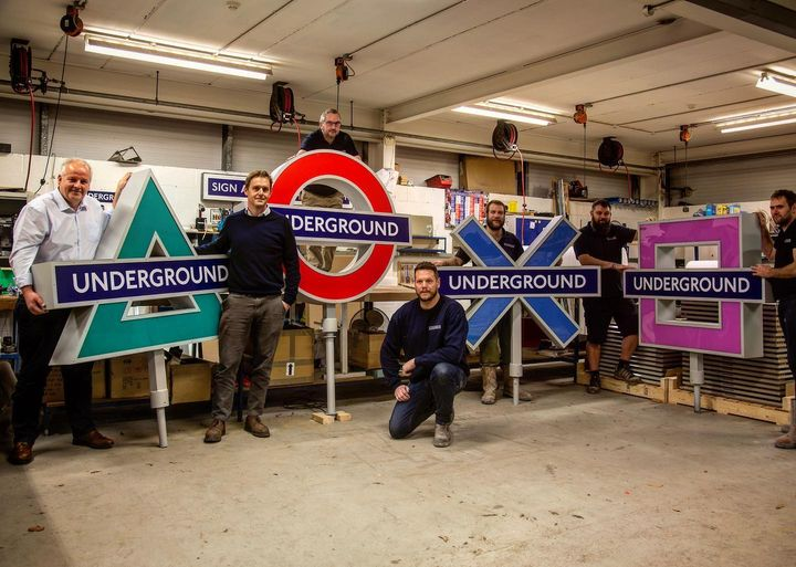 Picture of AJ Wells staff holding their PS5 themed signage for TFL