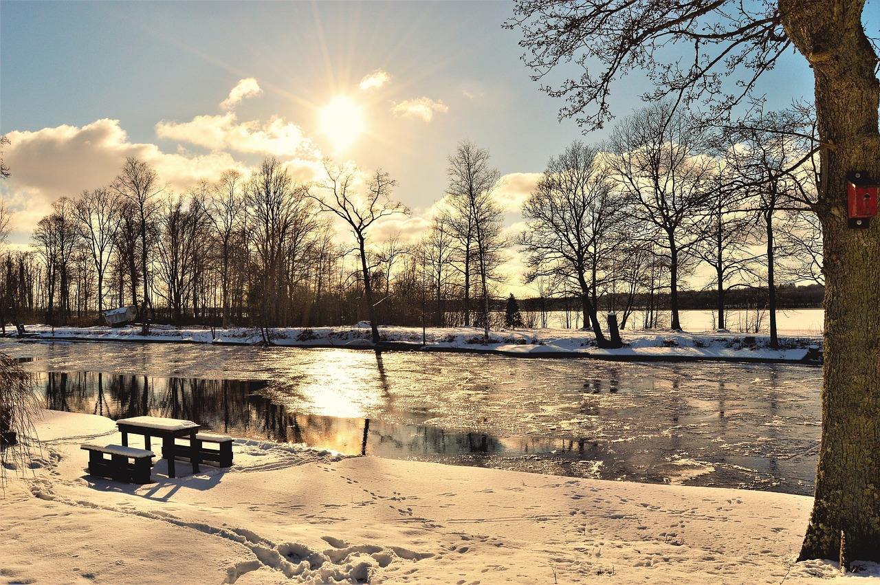 A view of a wintry landscape (riverside) with sun in the sky