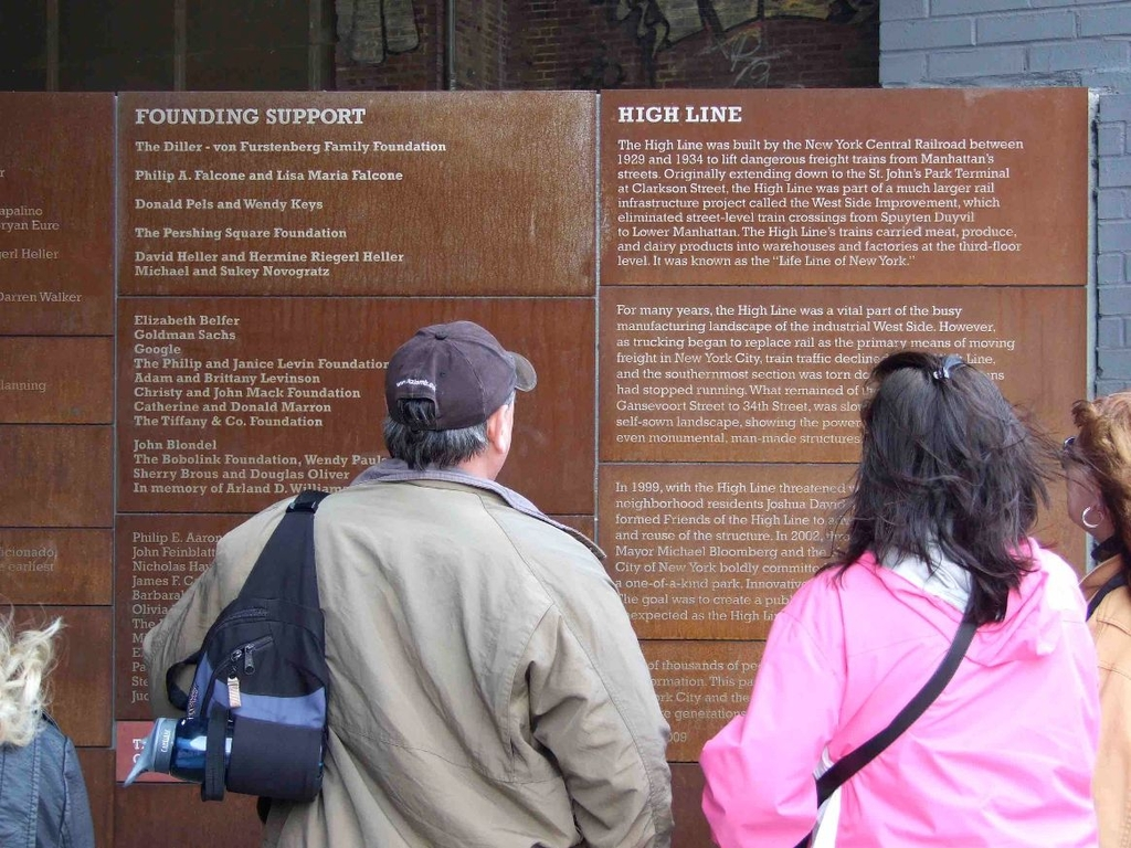 People looking at an outside information sign