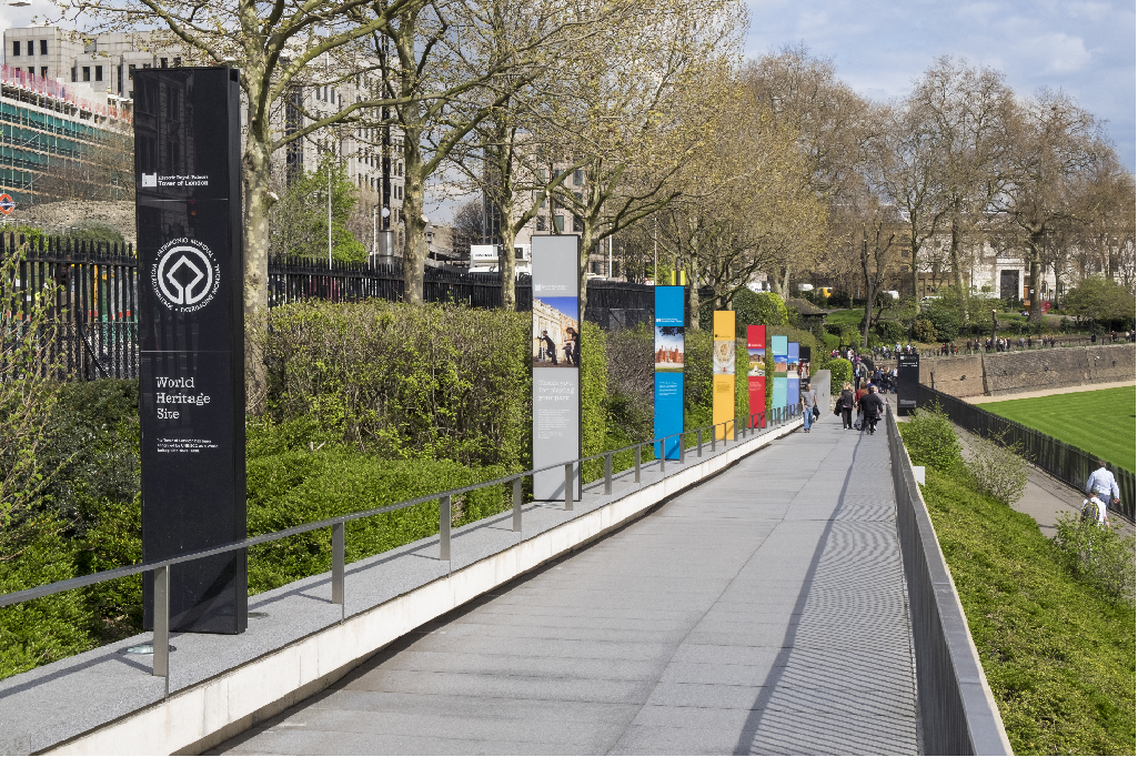 View of signage totems for the Tower of London down the side of an outdoor pathway