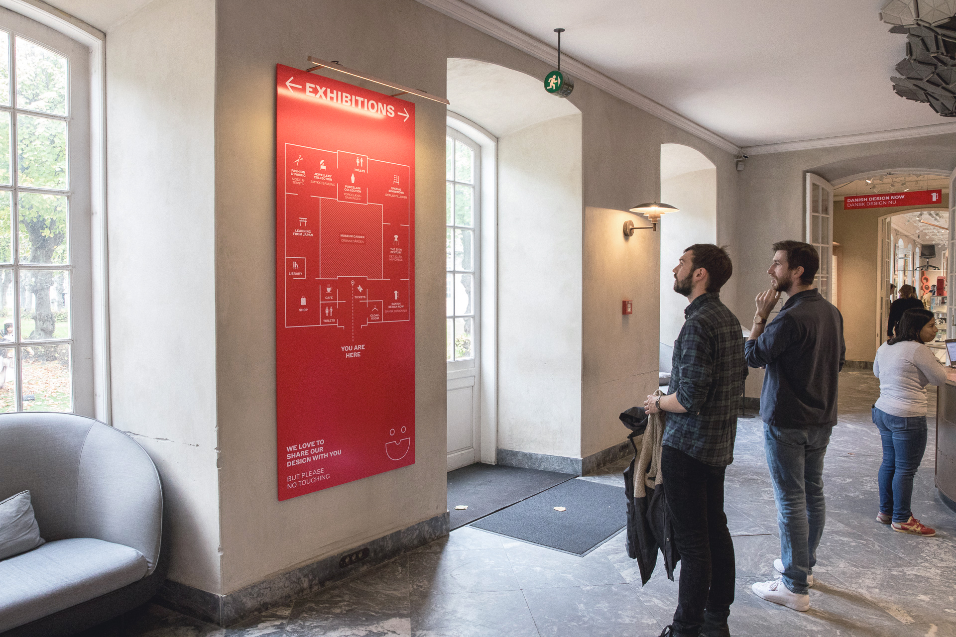 Interior view of visitors looking at a map of the museum layout as part of the wayfinding strategy for Designmusem Danmark